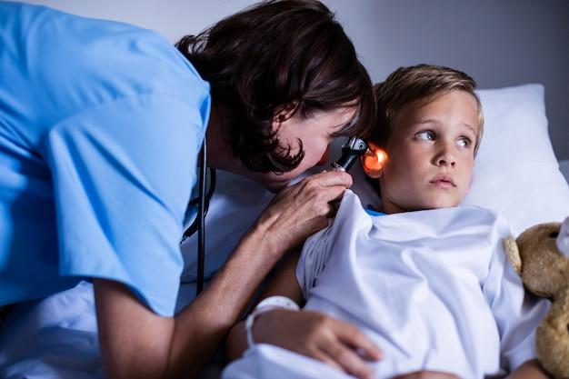 Vrouwelijke arts die geduldig oor met oorspiegel onderzoeken