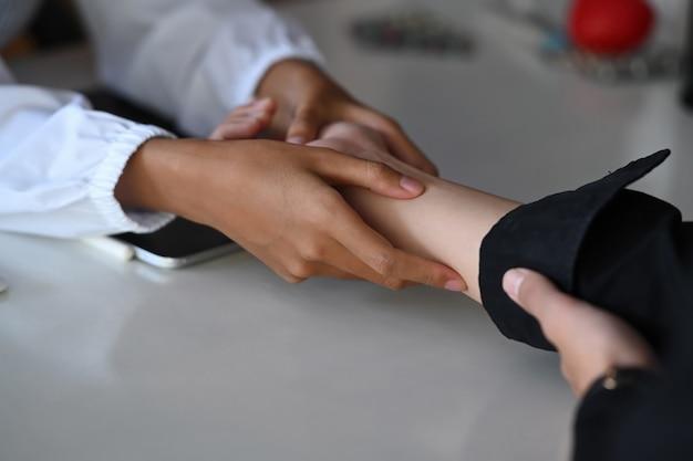 Vrouwelijke arts die geduldige handen maakt en haar patiënt troost.