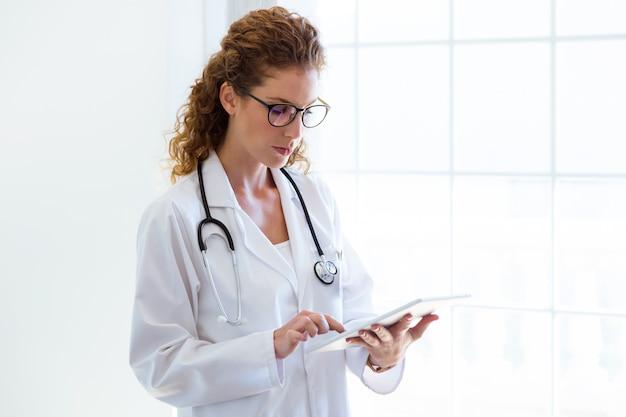 Vrouwelijke arts die haar digitale tablet in het bureau gebruikt.