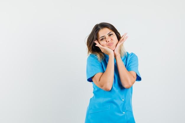 Vrouwelijke arts die haar gezicht op haar handen in blauw uniform dempt en er mooi uitziet