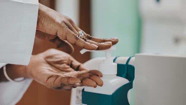 Vrouwelijke arts die haar handen desinfecteert