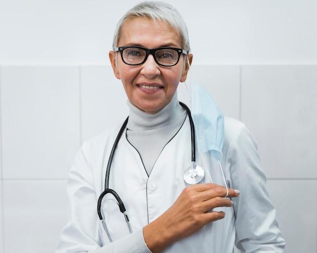 Vrouwelijke arts die haar medisch masker op de schouder houdt