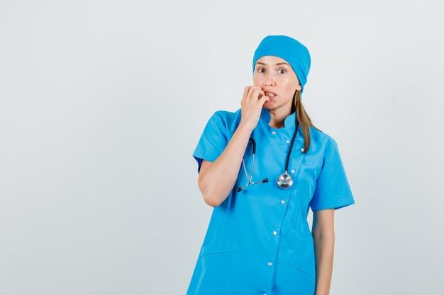 Vrouwelijke arts die hand dichtbij mond in blauw uniform houdt en bang kijkt