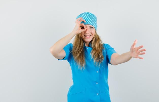 Vrouwelijke arts die hand met ok teken op oog in blauw uniform uitrekt en vrolijk kijkt.