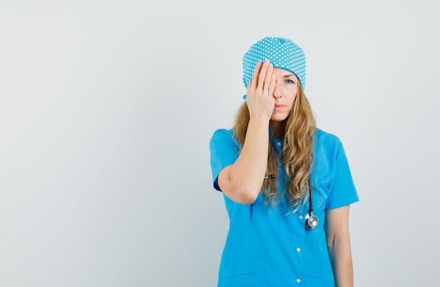 Vrouwelijke arts die hand op één oog in blauw uniform houdt