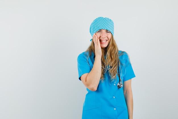 Vrouwelijke arts die hand op haar wang in blauw uniform houdt en depressief kijkt.