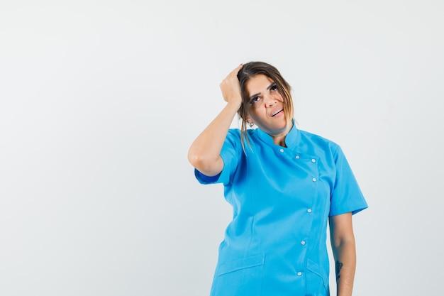 Vrouwelijke arts die hand op het hoofd houdt in blauw uniform en er attent uitziet