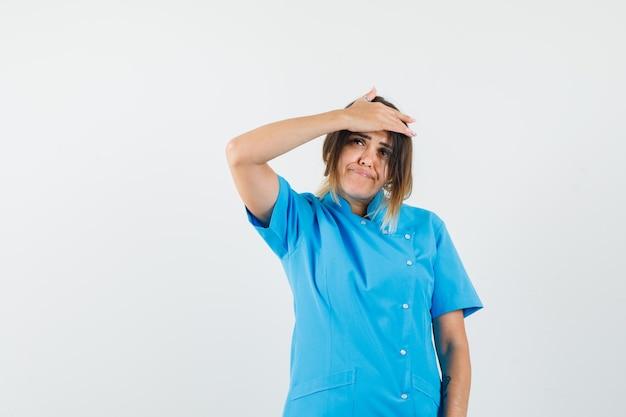 Vrouwelijke arts die hand op het voorhoofd houdt in blauw uniform en aarzelend kijkt