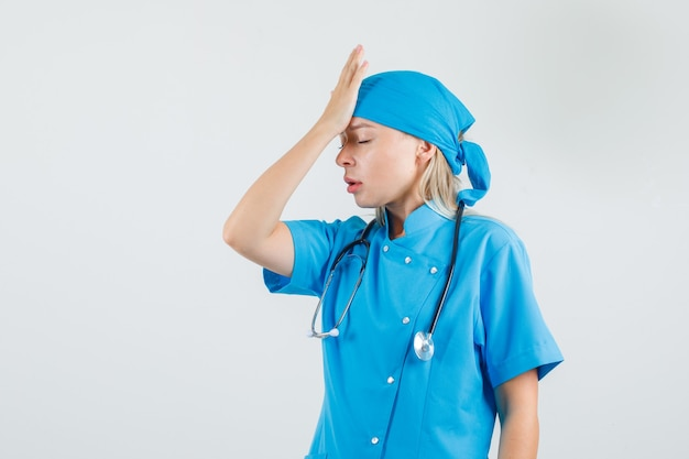 Vrouwelijke arts die hand op voorhoofd in blauw uniform houdt en moe kijkt