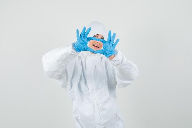 Vrouwelijke arts die hartgebaar in beschermend pak, handschoenen toont en gelukkig kijkt.