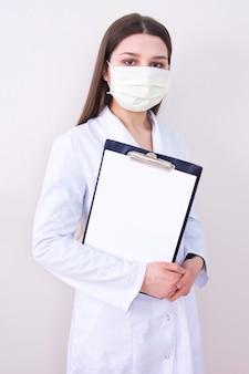 Vrouwelijke arts die het gezichtsmasker van de bescherming draagt.