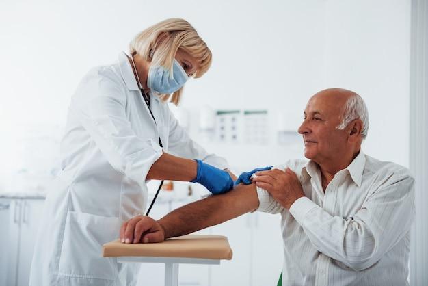 Vrouwelijke arts die hogere mannelijke patiënt met spuit in de kliniek injecteert.