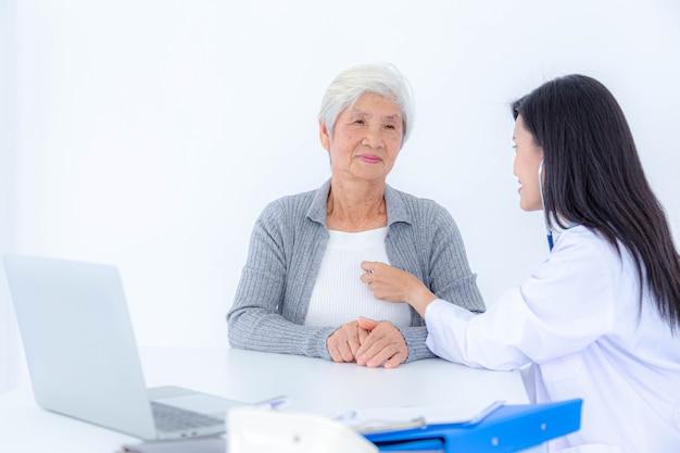 Vrouwelijke arts die hogere patiënt onderzoekt bij kliniek. gezondheidszorg, medisch, behandeling en ouderen ziekten concept.