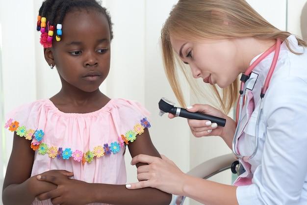 Vrouwelijke arts die huid van meisje met speciaal apparaat controleert.