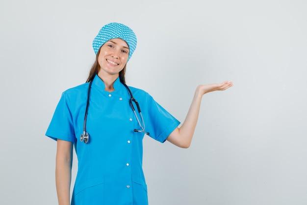 Vrouwelijke arts die iets met hand toont en in blauw uniform vooraanzicht glimlacht.