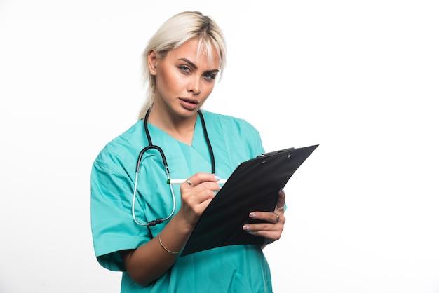 Vrouwelijke arts die iets op klembord schrijft met pen op witte achtergrond. hoge kwaliteit foto
