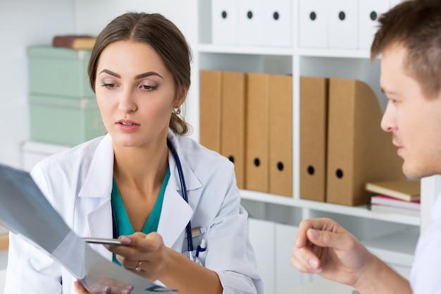 Vrouwelijke arts die iets toont aan haar mannelijke collega of patiënt. lichamelijk onderzoek, eh, ziektepreventie, wijkronde, bezoekcontrole, 911, remedie voorschrijven, gezond levensstijlconcept