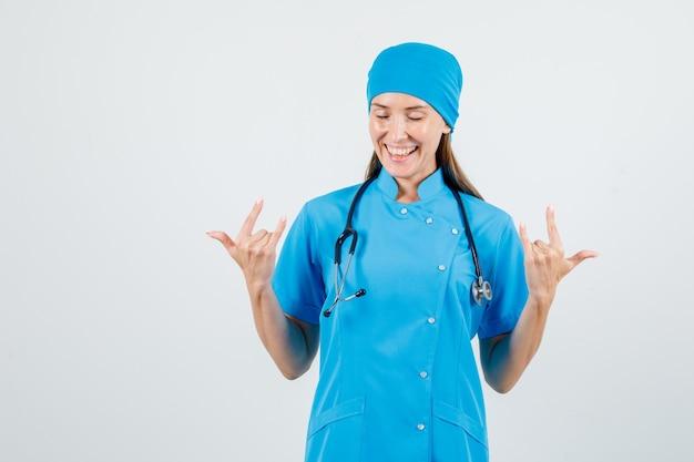 Vrouwelijke arts die 'ik hou van jou' gebaar in blauw uniform toont en er vrolijk uitziet