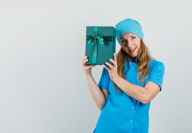 Vrouwelijke arts die in blauwe eenvormige huidige doos houdt en vrolijk kijkt