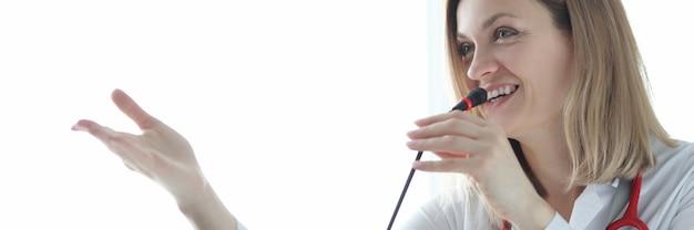 Vrouwelijke arts die in microfoon spreekt tijdens conferentie