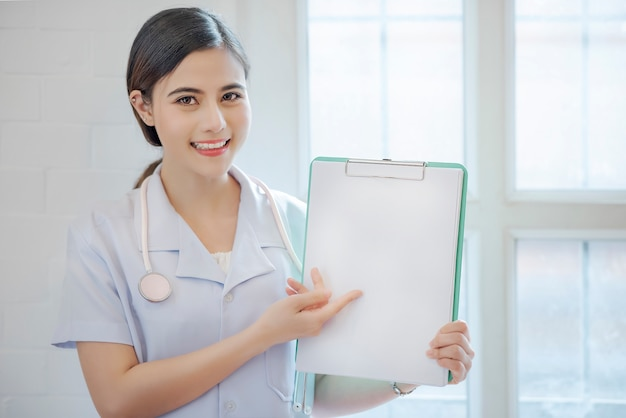 Vrouwelijke arts die klembord met copyspace toont.