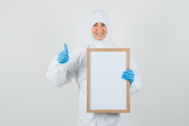 Vrouwelijke arts die leeg frame met duim omhoog in beschermingskostuum houdt