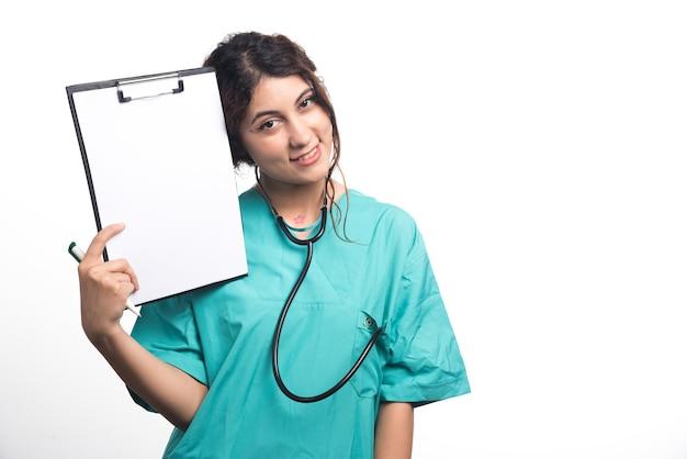Vrouwelijke arts die leeg klembord met pen en stethoscoop op witte achtergrond toont. hoge kwaliteit foto