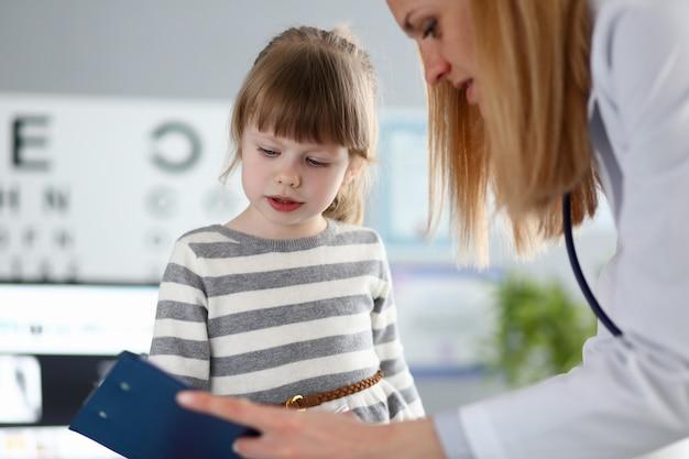 Vrouwelijke arts die leuke kleine patiënt luistert en registratieinformatie op klembordstootkussen schrijft