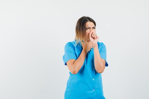 Vrouwelijke arts die lijdt aan hoest in blauw uniform en er ziek uitziet