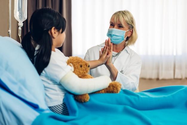 Vrouwelijke arts die masker draagt dat met weinig patiënt spreekt
