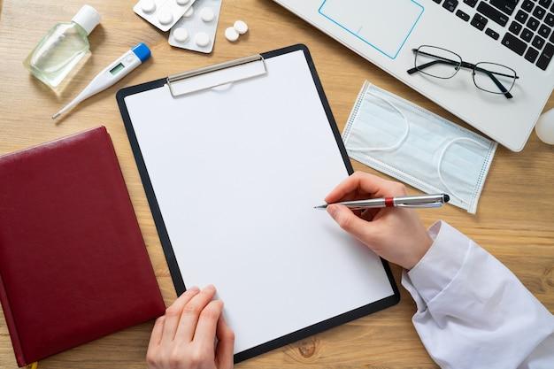 Vrouwelijke arts die medisch formulier op de ballpoint van de klembordholding en geneeskundefles vullen. gezondheidszorg en verzekeringen concept.