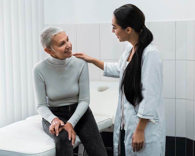 Vrouwelijke arts die met de patiënt spreekt