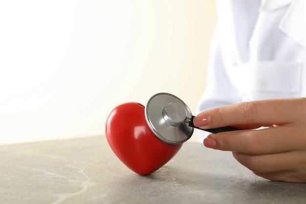 Vrouwelijke arts die met een stethoscoop hartslag controleert