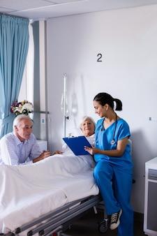 Vrouwelijke arts die met hoger paar over een rapport in de afdeling bespreken