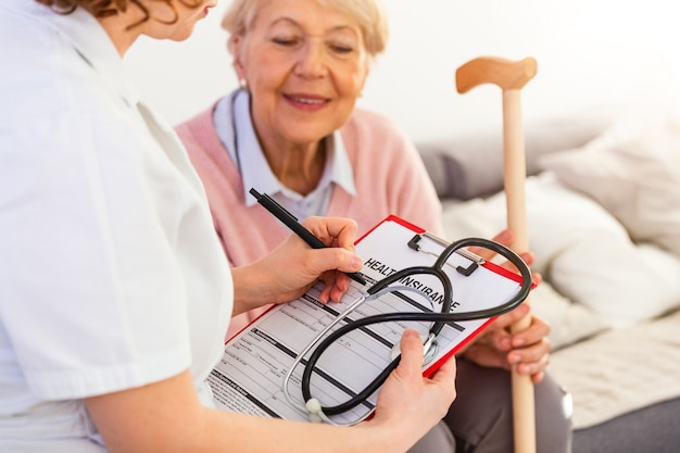 Vrouwelijke arts die met hogere patiënt spreekt