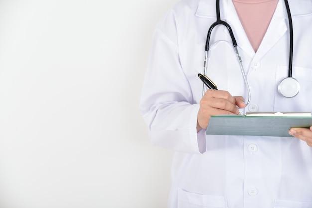 Vrouwelijke arts die met stethoscoop een klembord voor medische dossiers houdt. gezondheids controle.