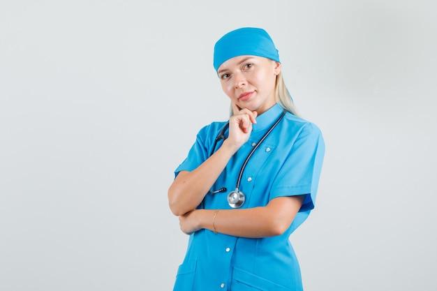 Vrouwelijke arts die met vinger op haar wang in blauw uniform denkt en hoopvol kijkt.