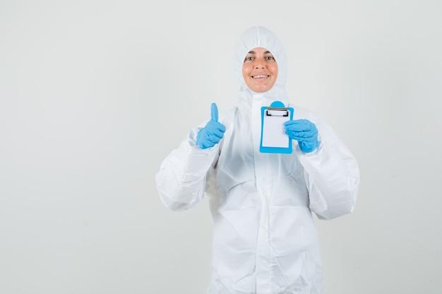 Vrouwelijke arts die miniklembord houdt, die duim in beschermingskostuum toont