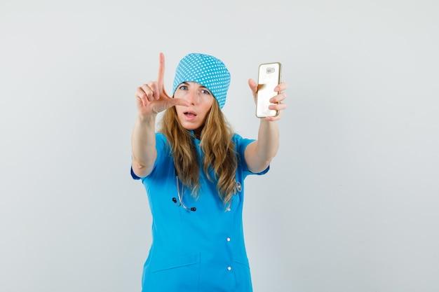Vrouwelijke arts die mobiele telefoon houdt en met vingers in blauw uniform gebaart