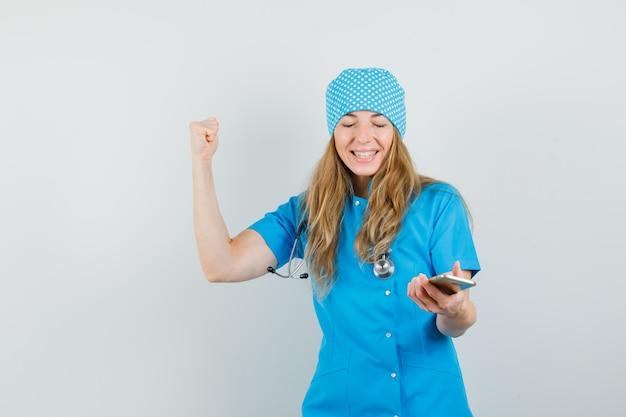 Vrouwelijke arts die mobiele telefoon met winnaargebaar in blauw uniform houdt en gelukkig kijkt.
