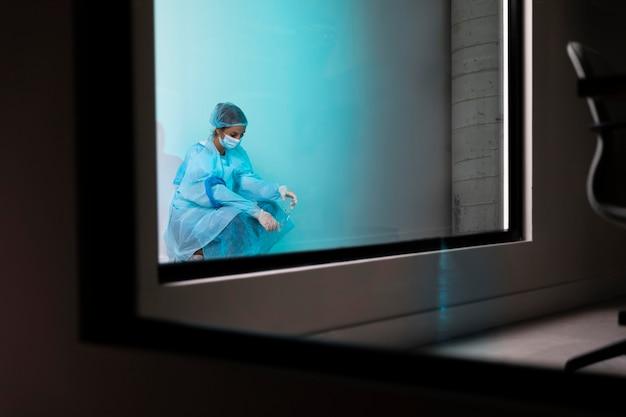 Vrouwelijke arts die moe met exemplaarruimte kijkt