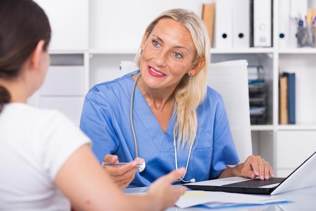 Vrouwelijke arts die naar klachten van patiënten luistert