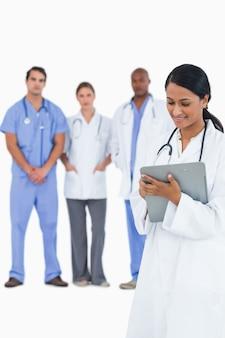 Vrouwelijke arts die nota's met personeelsleden achter haar neemt