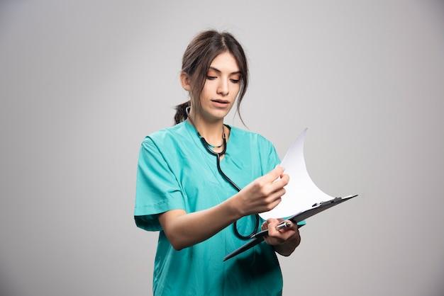 Vrouwelijke arts die nota's over klembord bekijkt