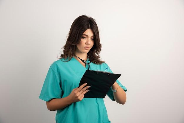 Vrouwelijke arts die notities van klembord leest