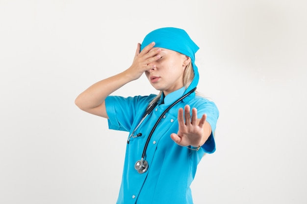 Vrouwelijke arts die ogen bedekt terwijl ze geen gebaar in blauw uniform toont en bang kijkt