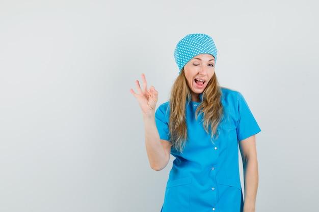 Vrouwelijke arts die ok gebaar en oog in blauw uniform toont