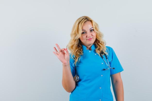 Vrouwelijke arts die ok gebaar in blauw uniform toont en tevreden kijkt