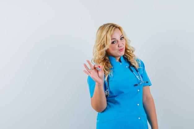 Vrouwelijke arts die ok gebaar in blauw uniform toont en tevreden ruimte voor tekst kijkt