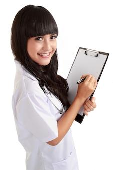 Vrouwelijke arts die op een klembord schrijft